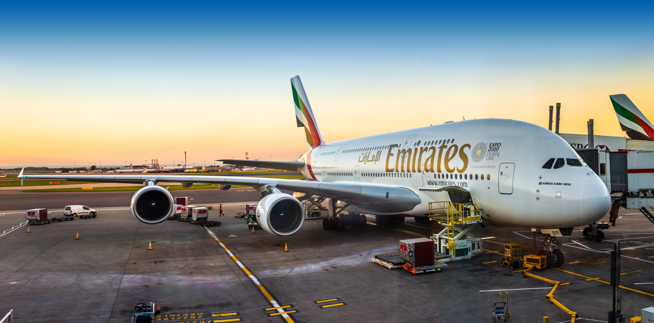An Emirates Airbus A380-800 super jumbo, the largest passenger aircraft in the world is waiting for passengers and loading at London Heathrow terminal 3 during sunset