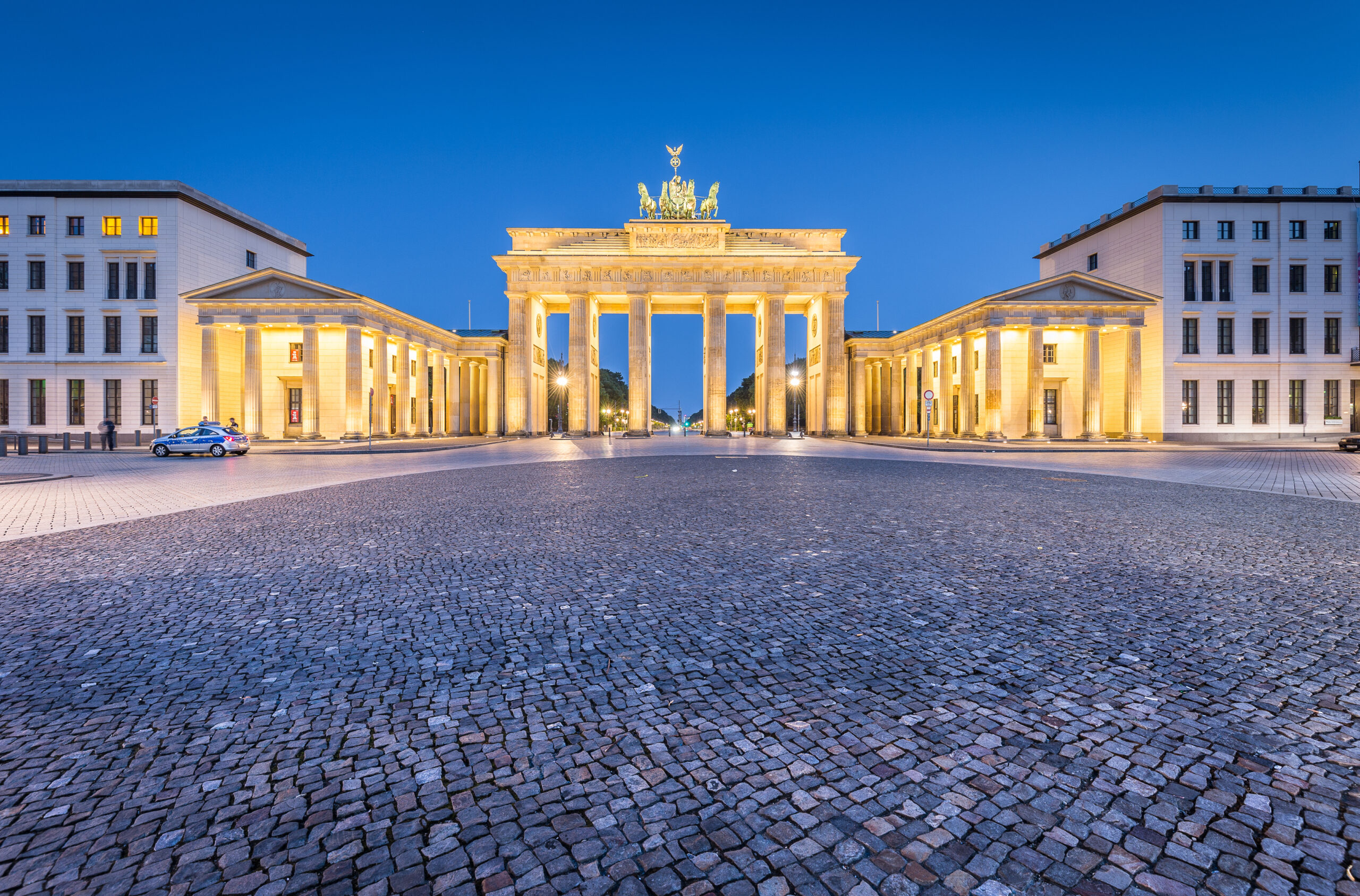 Classic panoramic view of historic Brandenburg Gate, Germany's most famous landmark and a national symbol, in post sunset twilight during blue hour at dusk in summer, central Berlin, Germany.