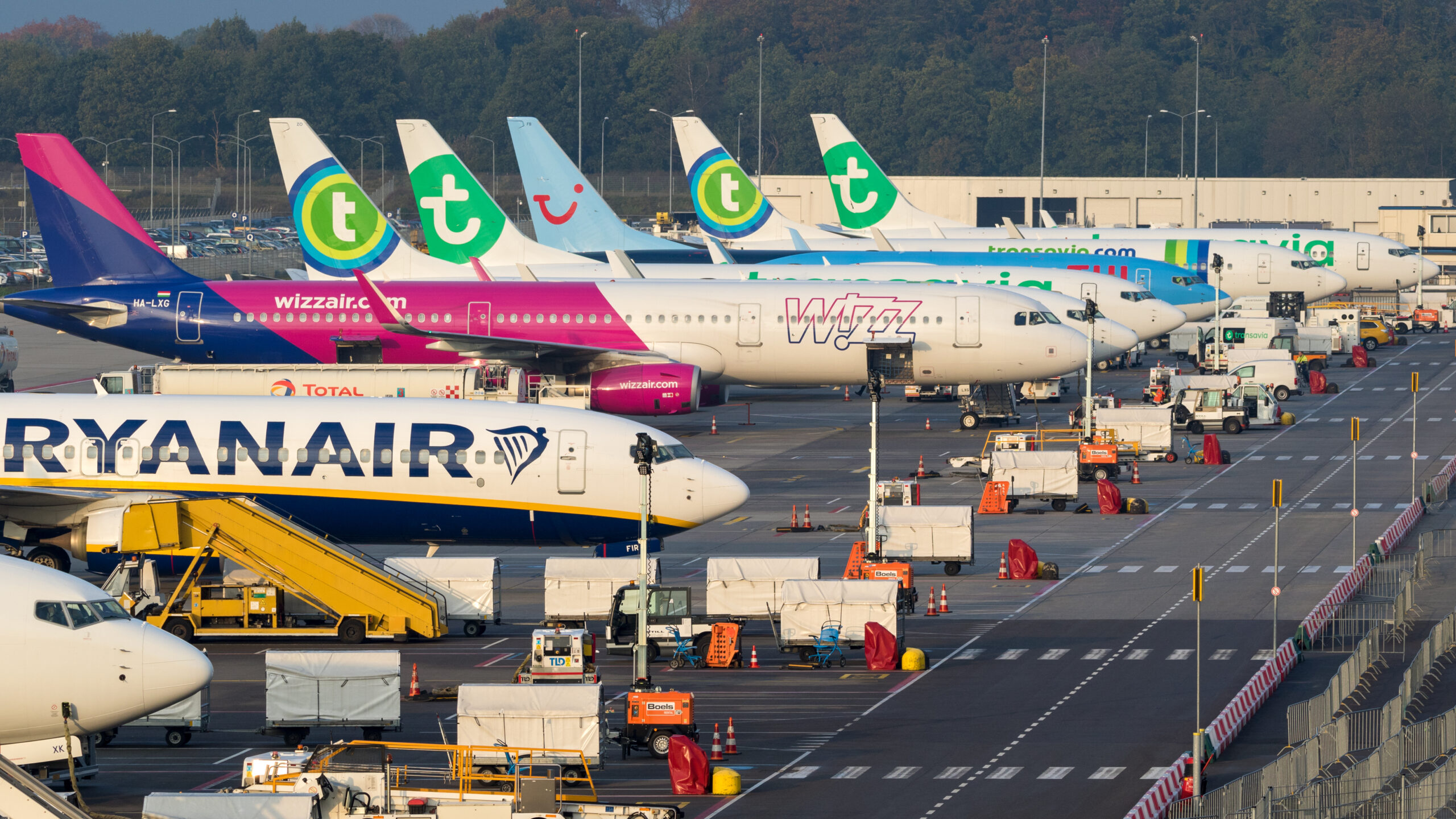 Various low-budget airline aircraft parked at the terminal of Eindhoven-Airport.