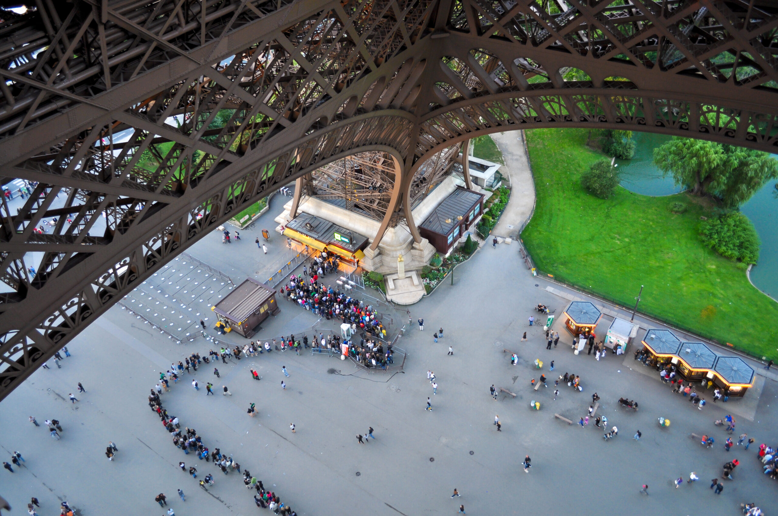 Crowds gather and form a long queue to visit the Eiffel tower.