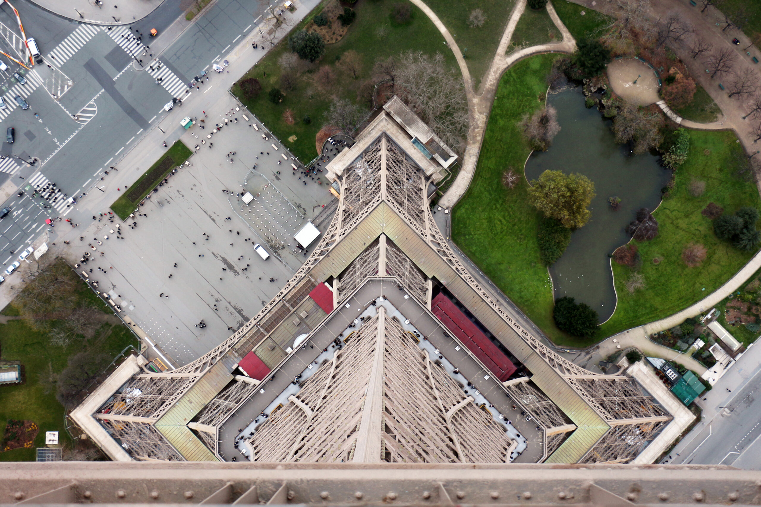 Vertical view from the top of the Eiffel tower in Paris, with perspective of the height of the tower and people in the park very far away below.