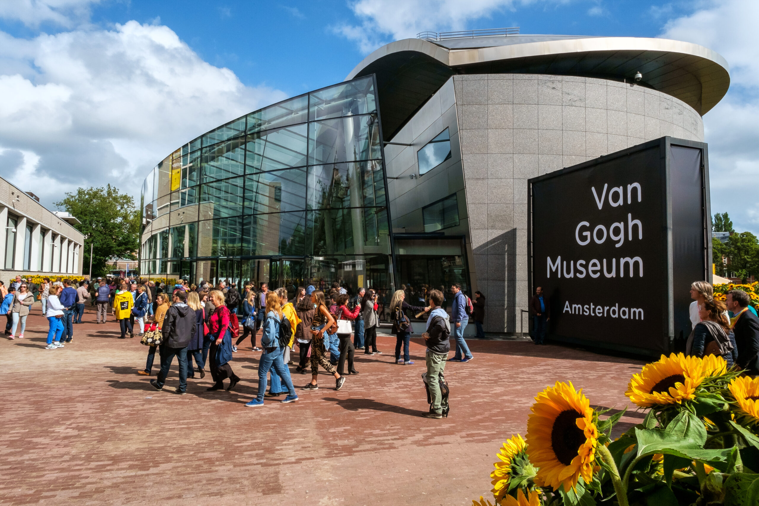 Crowd in front of the new wing of the Van Gogh Museum with sunflowers in the foreground.