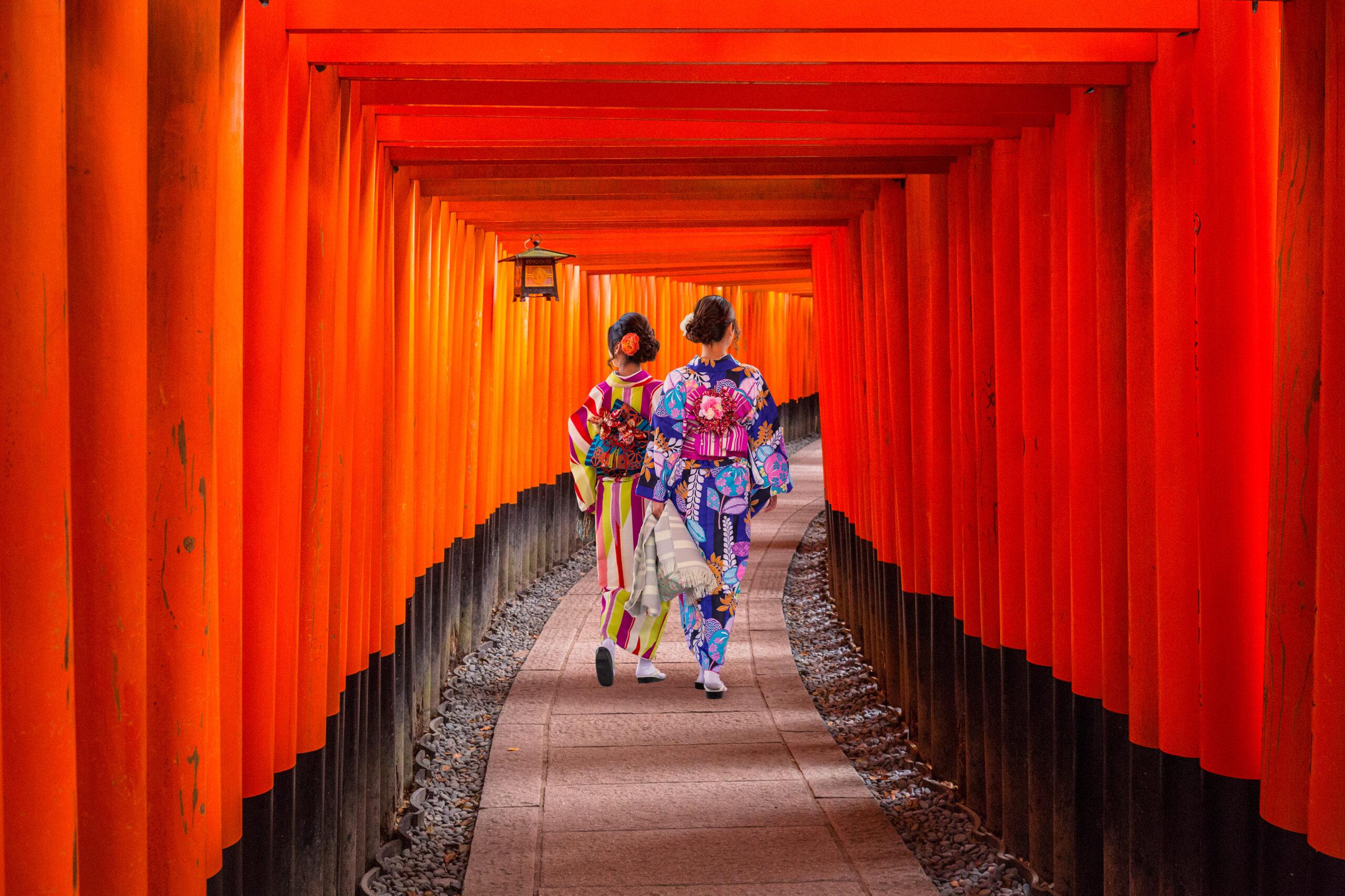 Women in traditional japanese kimonos walking at Fushimi Inari Shrine in Kyoto, Japan.
