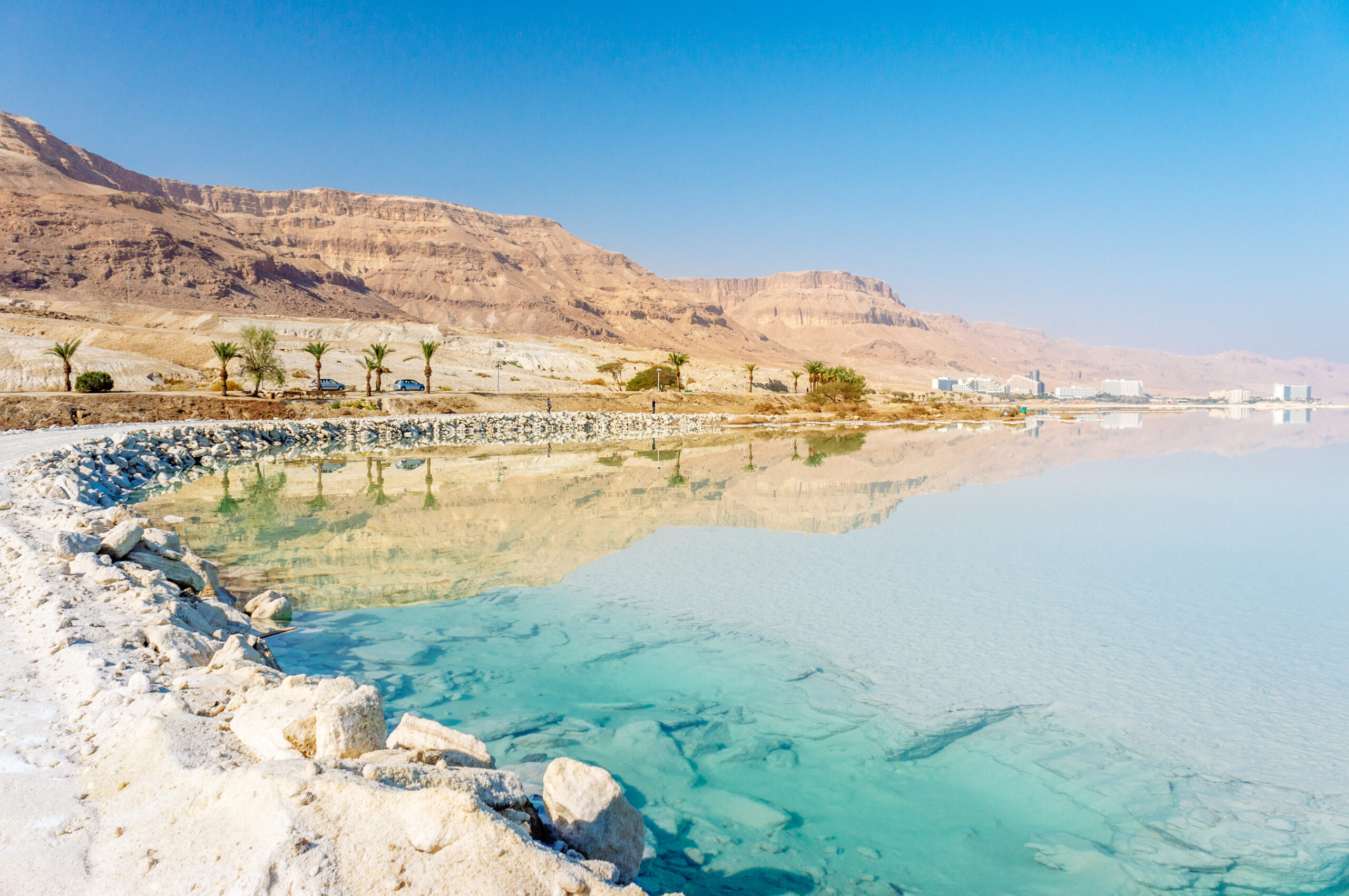 Dead Sea coastline with white salt beach and mountains at sunny day in Ein Bokek, Israel. White mineral salt shore at Dead sea, Israel.