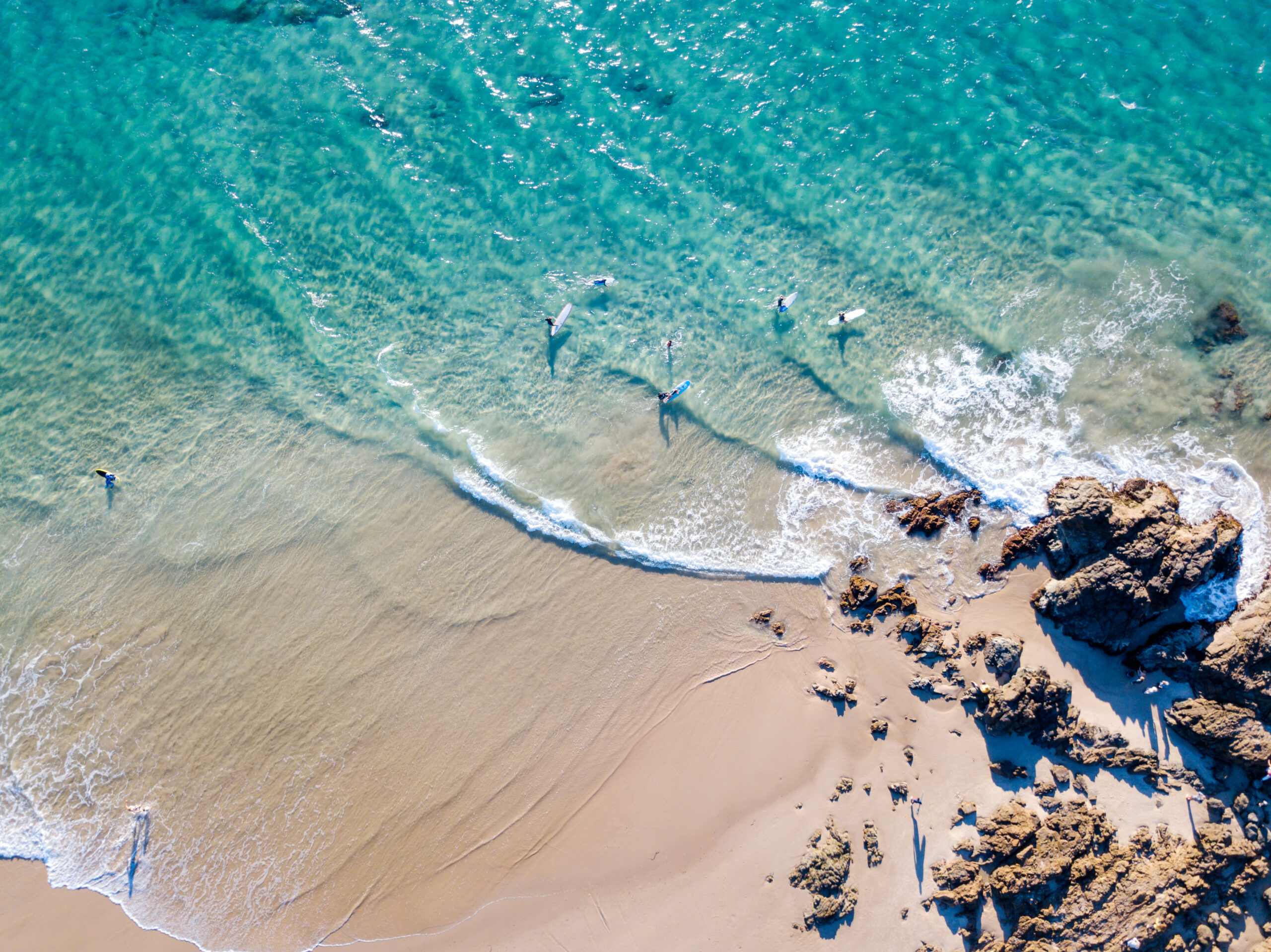 The Pass at Byron Bay from an aerial view with blue water.